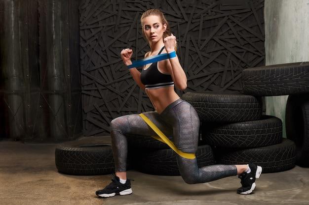 Mujer sexy en ropa deportiva usando una banda de resistencia en su rutina de ejercicios