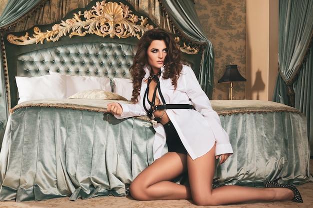 Mujer sexy y seductora con camisa de hombre y cinturón de pecho de cuero