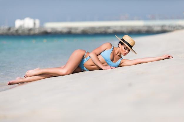 Mujer sexy en sombrero de paja relajante en la playa
