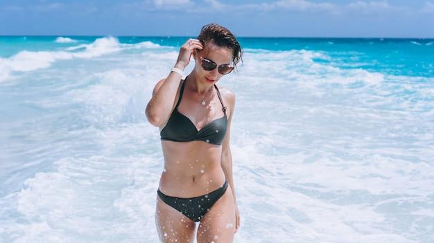 Mujer sexy en traje de baño bikini en el agua del océano