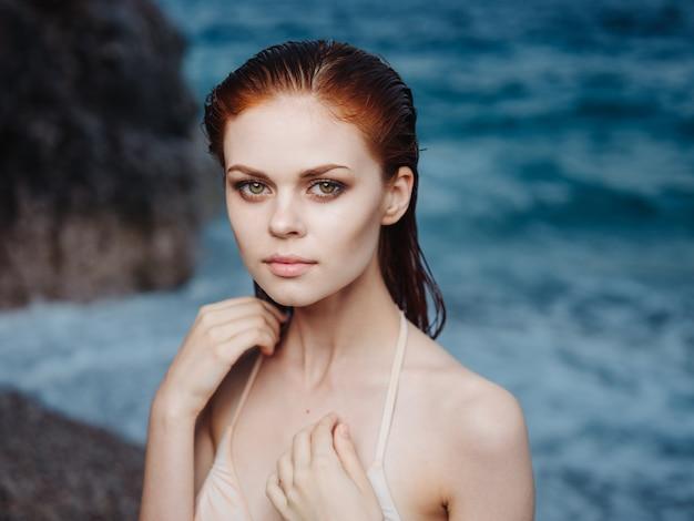 Mujer sexy en traje de baño blanco cerca del mar y la naturaleza de rocas de la playa de espuma.