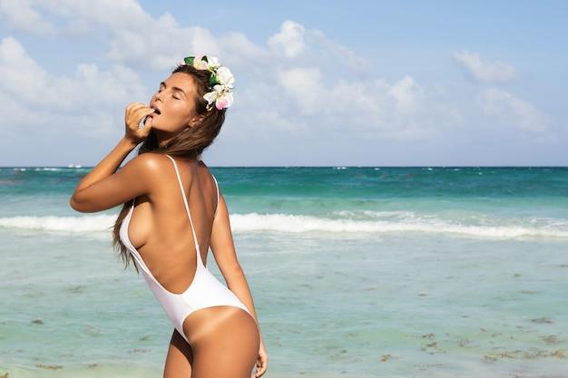 Mujer sexy en traje de baño blanco está posando en la playa