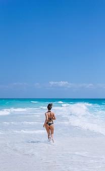Mujer sexy en traje de baño de pie en el océano