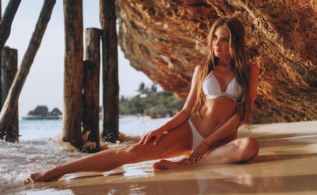 Mujer sexy en traje de baño tumbado junto al mar debajo de las cuevas