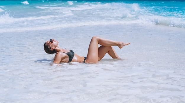Mujer sexy en traje de baño tumbado en el océano
