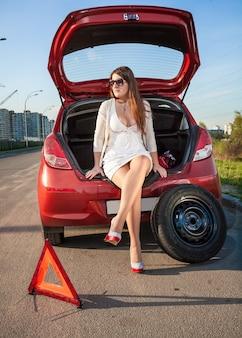 Mujer sexy en vestido corto esperando ayuda cerca de coche roto