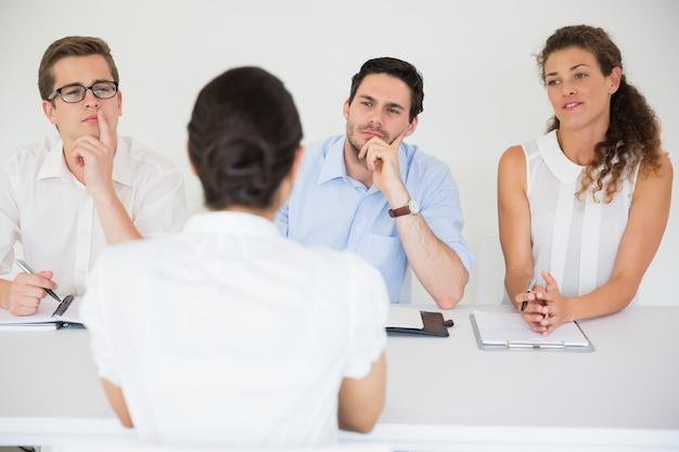 Mujer siendo entrevistada por gente de negocios.