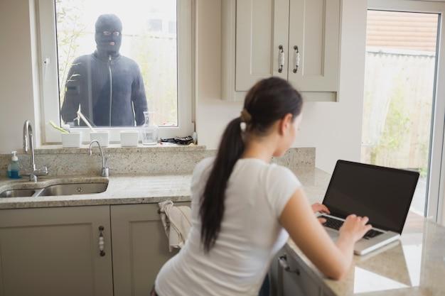 Mujer siendo observada por un ladrón a través de la ventana
