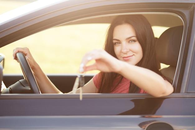 La mujer se sienta en el asiento del conductor, mantiene la mano en el volante, anuncia o vende automóviles. hermosa mujer morena conduce vehículo