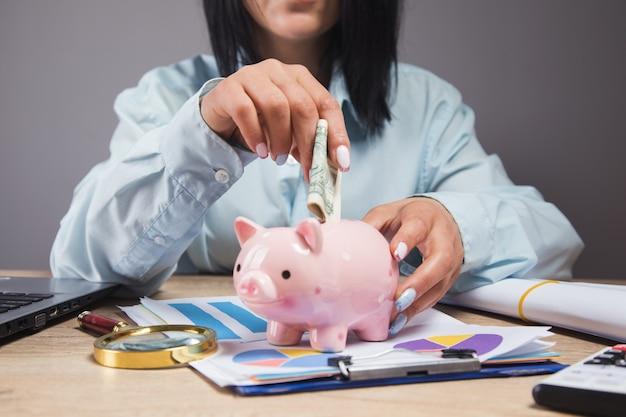 Una mujer se sienta frente a una mesa de trabajo y tira dinero en una alcancía
