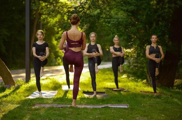 La mujer se sienta en pose de yoga en la hierba, entrenamiento en grupo.