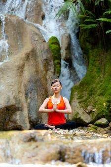 La mujer se sienta en la posición de loto gesticulando zen. concepto de estilo de vida saludable y la relajación.