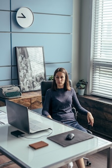 La mujer se sienta en su escritorio y mira la pantalla del portátil.
