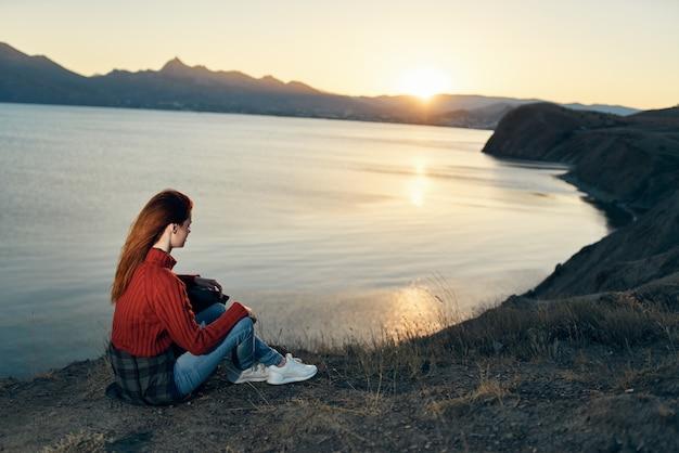 La mujer se sienta en el suelo en la naturaleza en las montañas cerca de la puesta de sol de la aventura del mar. foto de alta calidad