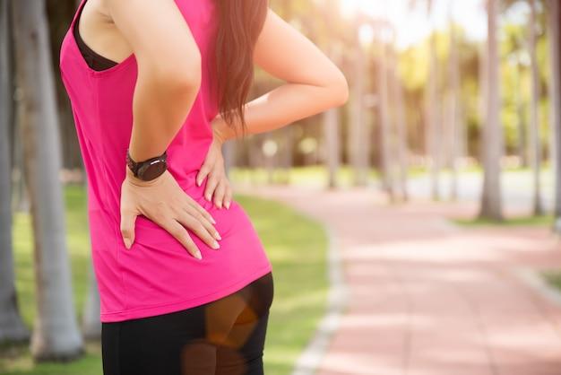 Mujer siente dolor en la espalda y la cadera mientras hace ejercicio, concepto de salud.