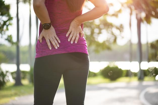 La mujer siente dolor en la espalda y la cadera mientras hace ejercicio