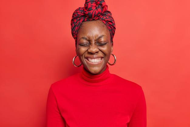La mujer se siente muy feliz sonríe con dientes sonríe a la cámara disfruta de agradables palabras vestidas con ropa casual plantea en rojo vivo