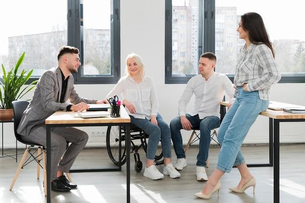 Mujer en silla de ruedas y compañeros de trabajo en la oficina conversando