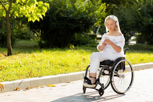 Mujer en silla de ruedas escuchando música fuera