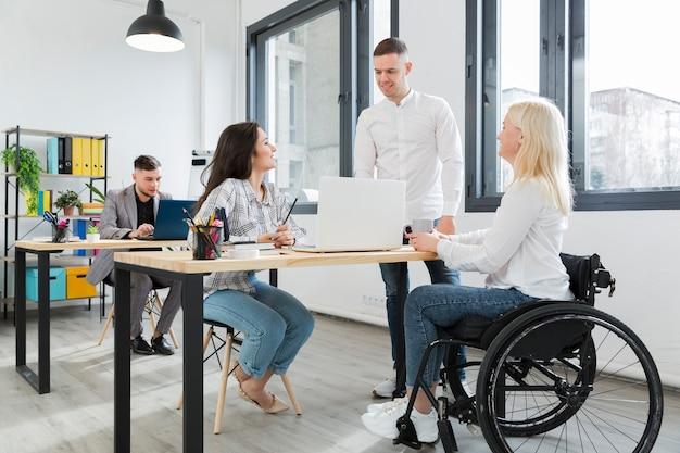 Mujer en silla de ruedas en la oficina junto con compañeros de trabajo