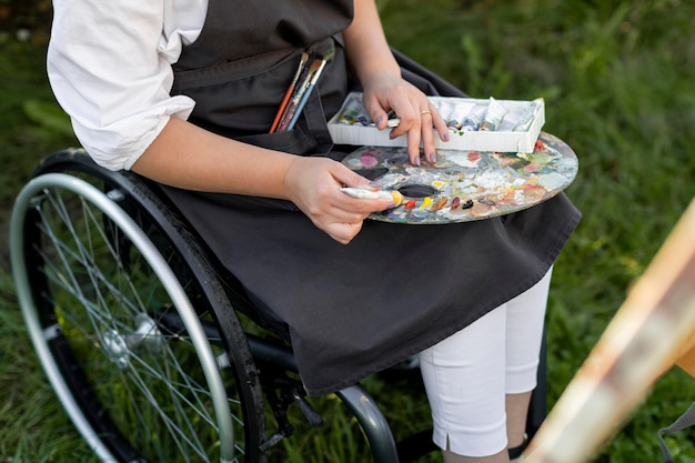 Mujer en silla de ruedas con paleta de pintura en la naturaleza