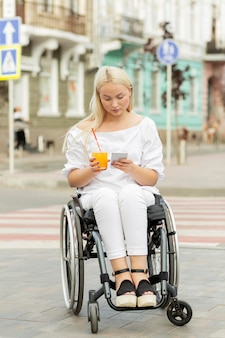 Mujer en silla de ruedas con smartphone mientras toma una copa