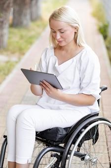 Mujer en silla de ruedas con tableta fuera