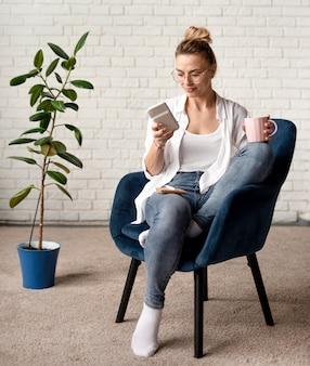 Mujer, en, silla, verificar móvil