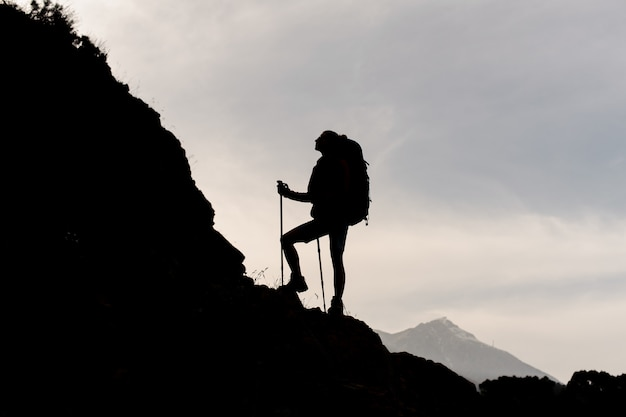 Mujer de silueta de pie sobre las rocas con mochila de senderismo y bastones