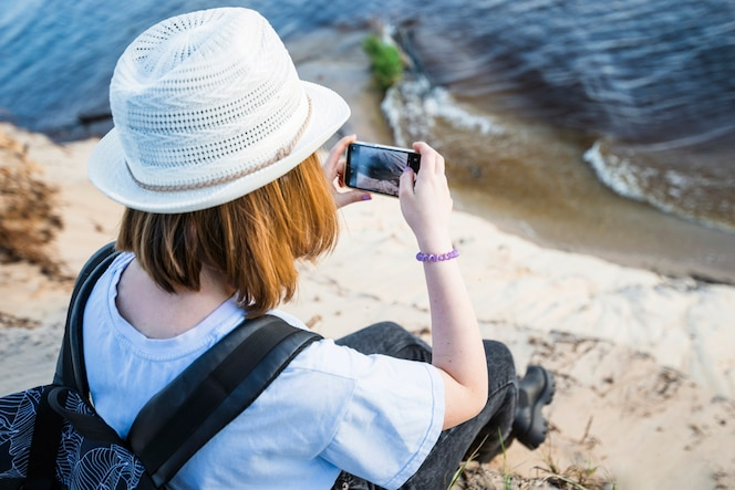 Mujer sin rostro tomando foto del mar