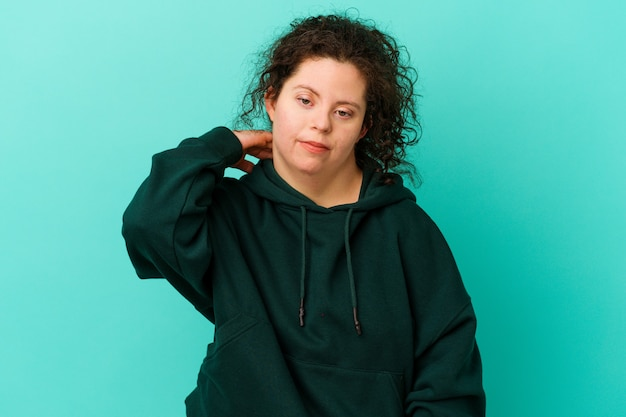 Mujer con síndrome de down aislada que tiene dolor de cuello debido al estrés, masajeando y tocándolo con la mano.