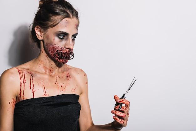 Mujer siniestra con la boca cosida y tijeras