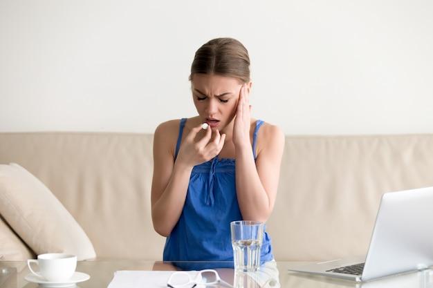 Mujer sintiendo dolor de cabeza y bebiendo pastilla en casa