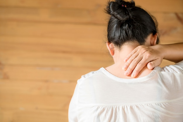 Mujer sintiéndose agotada y sufriendo de dolor de cuello.
