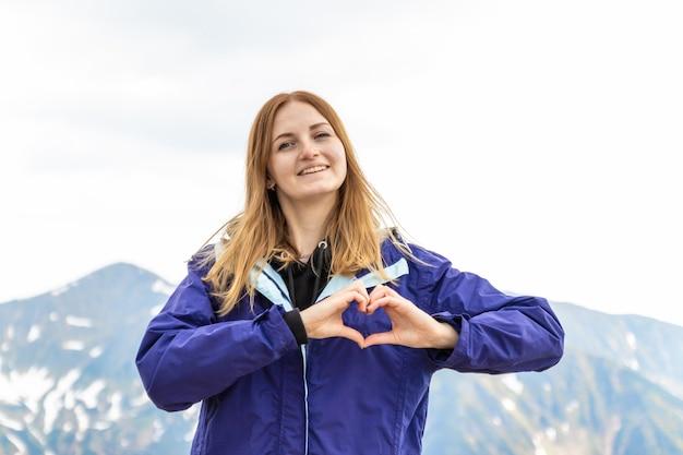 Mujer sintiéndose feliz haciendo una forma de corazón con sus manos contra el paisaje de rocas de montaña