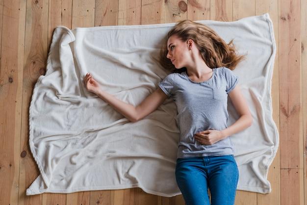 Mujer sintiéndose sola mientras yacía sola en tela escocesa