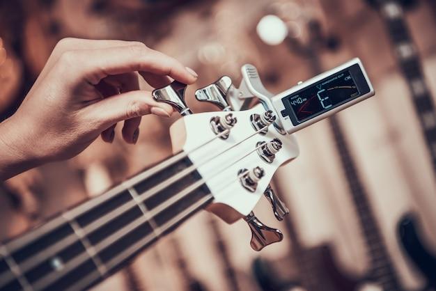 La mujer sintoniza la guitarra con el clip del sintonizador girando en el diapasón.