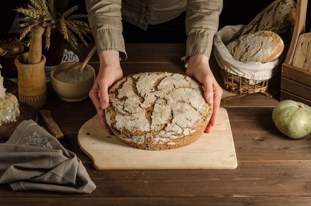 Una mujer sirve delicioso pan de centeno integral recién horneado.