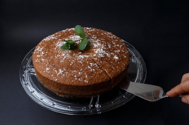 Mujer sirviendo un pastel de chocolate con decoración de azúcar con una espátula