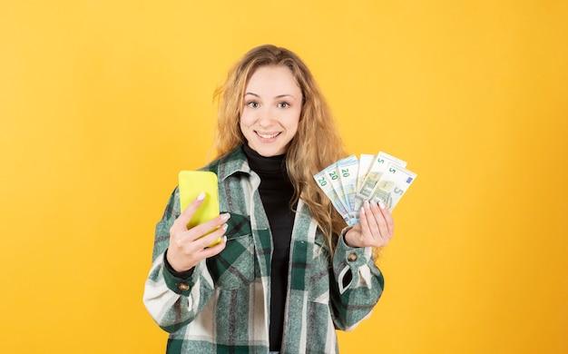 Mujer con smarthpone y billetes, concepto de compra online, guardar concepto