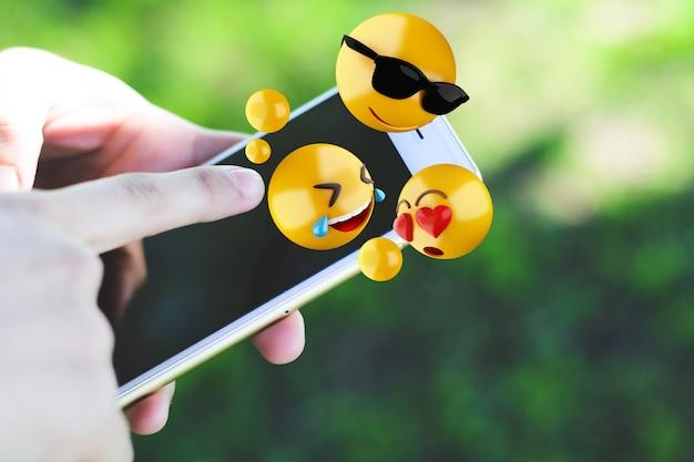 Mujer con smartphone enviando emojis.