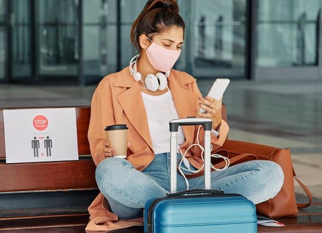Mujer con smartphone y equipaje en el aeropuerto durante la pandemia