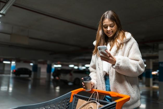 Mujer con smartphone en manos y carrito de compras