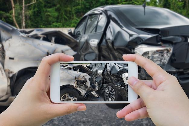 Mujer con smartphone tomar foto de accidente automovilístico en la carretera