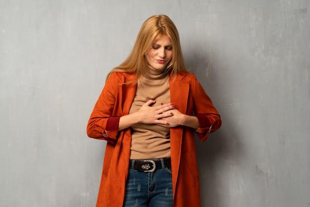 Mujer sobre fondo texturizado que tiene un dolor en el corazón