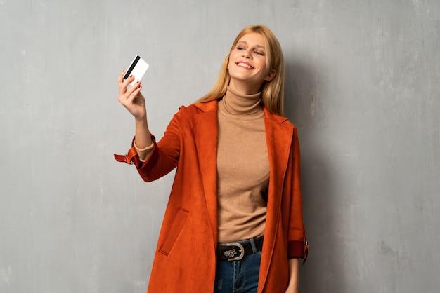 Mujer sobre fondo texturizado con teléfono inteligente roto con problemas