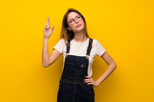 Mujer sobre muro amarillo con dedos cruzándose y deseando lo mejor.