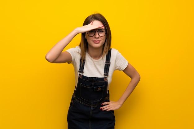 Mujer sobre pared amarilla mirando lejos con la mano para mirar algo