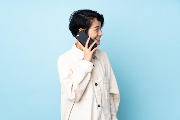 Mujer sobre pared hablando por teléfono