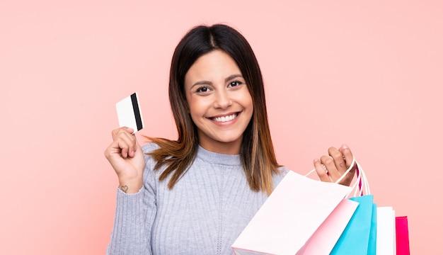 Mujer sobre pared rosa sosteniendo bolsas de compra y una tarjeta de crédito